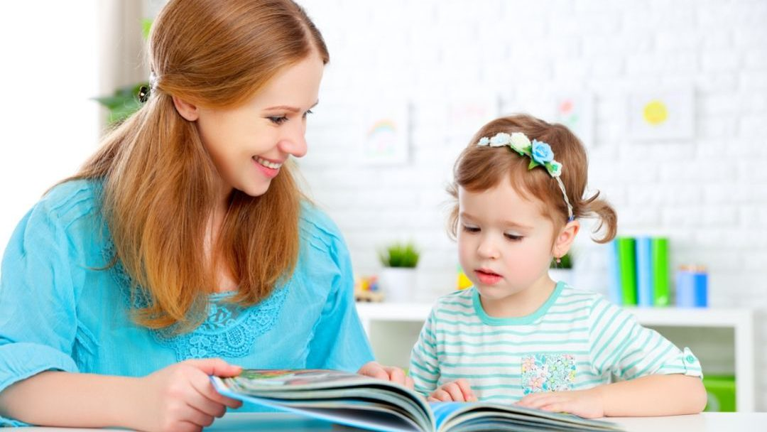 Mother reading wordless books to AAC learners